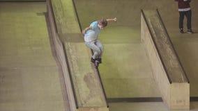De dia van de rolschaatser op rand van springplank op wedstrijd in skatepark tekortkoming uitdaging competition stock videobeelden