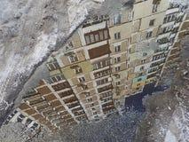 De diagonale bezinning van het gebouw is bruin in een vulklei op het asfalt, langs de rand van de vulkleistrook van grijze sneeuw Royalty-vrije Stock Afbeeldingen