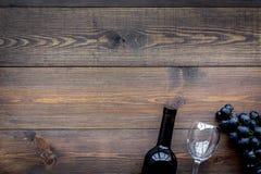 De dichtbijgelegen bos van de wijnfles van zwarte druiven op donkere houten hoogste mening als achtergrond copyspace Royalty-vrije Stock Foto