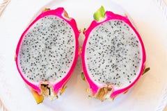 De dichte mening van twee sneed wit draakfruit die roze schil en zwarte die zaden tonen, op plaat wordt gecentreerd stock afbeelding