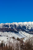 De dichte mening van zonovergoten Bucegi-bergenrand met steile die hellingen door sneeuw bij zonsopgang worden behandeld, de berg Royalty-vrije Stock Fotografie