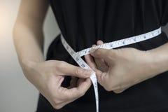 De dichte omhooggaande vrouwen die van het dieetconcept tailleomtrek meten stock foto