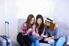 De dichte vrouwelijke tablet van het vriendengebruik en heeft pret, zit op laag in ro royalty-vrije stock afbeelding