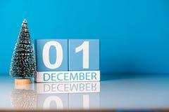 1 de diciembre día 1 del mes de diciembre, calendario con poco árbol de navidad en fondo azul Flor en la nieve Espacio vacío Imagen de archivo libre de regalías
