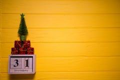 31 de diciembre día 31 de sistema de diciembre en calendario de madera en fondo de madera amarillo del tablón Imágenes de archivo libres de regalías