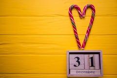 31 de diciembre día 31 de sistema de diciembre en calendario de madera en fondo de madera amarillo del tablón Fotos de archivo libres de regalías