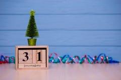 31 de diciembre día 31 de sistema de diciembre en calendario de madera en fondo de madera azul del tablón Fotografía de archivo