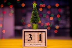 31 de diciembre día 31 de sistema de diciembre en calendario de madera en fondo borroso del bokeh de la guirnalda con un árbol de Fotos de archivo