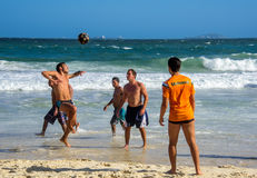 6 de diciembre de 2016 Tres hombres brasileños que juegan a fútbol de la playa en el movimiento en el fondo de ondas en la playa  Imagen de archivo