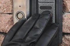 De dief die zwarte handschoenen dragen roept de intercom met de camera en het drukken van de knoop, controle als de eigenaars een stock foto