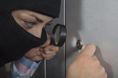 De dief probeert om het slot te openen gebruikend het slot stock fotografie