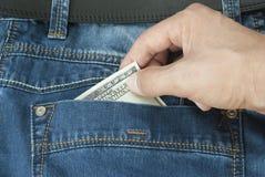 De Dief van de hand trekt de jeans met een dollar Stock Foto