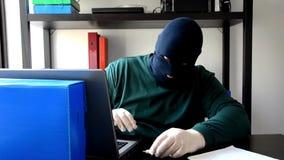 De dief in zwart masker neemt usb flashgeheugen in computer op stock footage