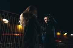 De diefstalscène van de nachtstraat: mens die jonge vrouwelijke zak weghalen stock foto's