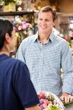 De dienende klant van de bloemist stock afbeelding
