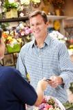De dienende klant van de mens in bloemist royalty-vrije stock afbeeldingen
