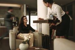 De dienende koffie van het bedrijfszitkamerpersoneel aan vrouwelijke reiziger royalty-vrije stock fotografie