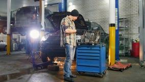 De dienst van de auto Brutale mechanische mens die zich door de auto bevinden die een instrument houden Het uittrekken van de han stock footage
