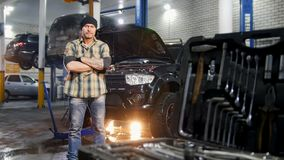 De dienst van de auto Brutale mechanische mens die zich door de auto bevinden die een instrument houden Hulpmiddelgeval op een vo stock footage