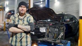 De dienst van de auto Brutale mechanische mens die zich door de auto bevinden die een moersleutel houden stock footage