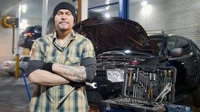 De dienst van de auto Brutale mechanische mens die zich door de auto bevinden die een moersleutel houden Het kijken in de camera stock video