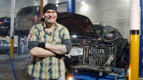 De dienst van de auto Brutale mechanische mens die zich door de auto bevinden Grijnzen en glimlachen stock videobeelden