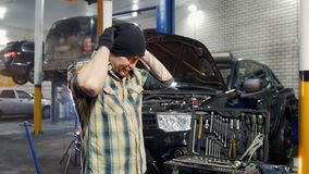 De dienst van de auto De brutale mechanische mens die zich door de auto bevinden, zet op een zwarte hoed en het kiezen van een hu stock videobeelden