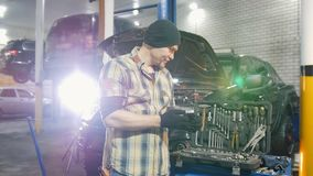 De dienst van de auto Brutale mechanische mens die zich door de auto en de glimlachen bevinden Verwijdert de het werk attributen stock video