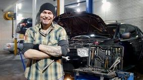De dienst van de auto Brutale mechanische mens die zich door de auto en de grijnzen bevinden stock video