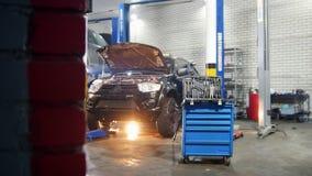De dienst van de auto Mechanische mens die een auto herstellen Hij komt aan het hulpmiddelgeval, die het hulpmiddel veranderen en stock video