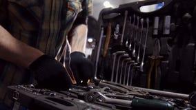 De dienst van de auto Mechanische mens die de juiste groottemoersleutel in het hulpmiddelgeval en de gangen weg kiezen stock footage