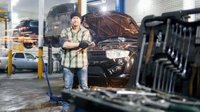 De dienst van de auto Mechanische mens die zich door de auto bevinden die een hulpmiddel houden en in de camera kijken stock footage