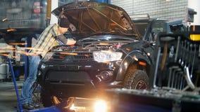 De dienst van de auto Mechanische mens die zich door de auto met open kap bevinden en met een hulpmiddel werken stock videobeelden
