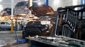 De dienst van de auto Mechanische mens die zich door de auto met open kap bevinden en met een hulpmiddel werken Hulpmiddelgeval o stock footage