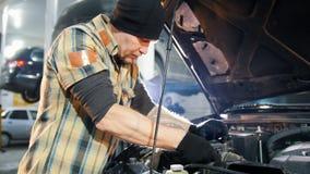 De dienst van de auto Mechanische mens die zich door de auto met open kap bevinden en auto met een moersleutel herstellen stock footage