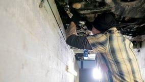 De dienst van de auto Mechanische mens die zich in inspectiekuil bevinden en met een hulpmiddel werken stock footage