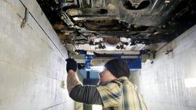 De dienst van de auto Mechanische mens die zich in inspectiekuil bevinden en met een moersleutel werken stock videobeelden
