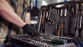 De dienst van de auto De mechanische mens loopt aan het hulpmiddelgeval, weg kiezend de juiste groottemoersleutel en de gangen stock footage