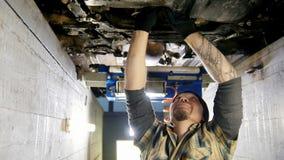 De dienst van de auto Mechanische mens met een tatoegering die zich in inspectiekuil bevinden en met een hulpmiddel werken stock videobeelden