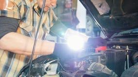 De dienst van de auto De mechanische mens spint de noten met een moersleutel stock video