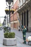De dienst van het stadsgroen het water geven bloemen in mand op lichte polen stock foto's