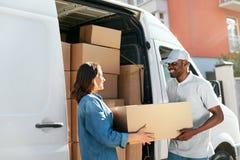 De dienst van de levering De Vrouw van koeriersdelivering package to dichtbij Auto royalty-vrije stock afbeelding