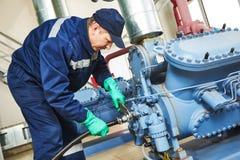De dienstarbeider bij industriële compressorpost Royalty-vrije Stock Afbeeldingen