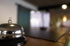 De dienstklok plaatsbepaling bij ontvangst Zilveren alarmbel op lijst, receptionnisten aangaande achtergrond royalty-vrije stock fotografie