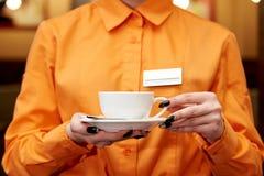 De dienstpersoneel in oranje overhemd met een kop van koffie royalty-vrije stock foto