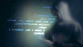 De digitale die informatie wordt op de muur met een hakker in vermomming dichtbij het wordt ontworpen stock footage