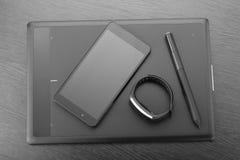 De digitale grafische tablet van de kunstraad met naald, smartphone en activiteitendrijver op een donkere houten oppervlakte Hoog Royalty-vrije Stock Foto
