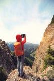 de digitale tablet die van het wandelaargebruik foto op berg piekklip nemen Stock Afbeelding