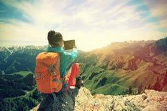de digitale tablet die van het wandelaargebruik foto op berg piekklip nemen Stock Foto
