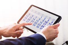 De Digitale Tablet van Businesspersonusing calendar on royalty-vrije stock afbeelding